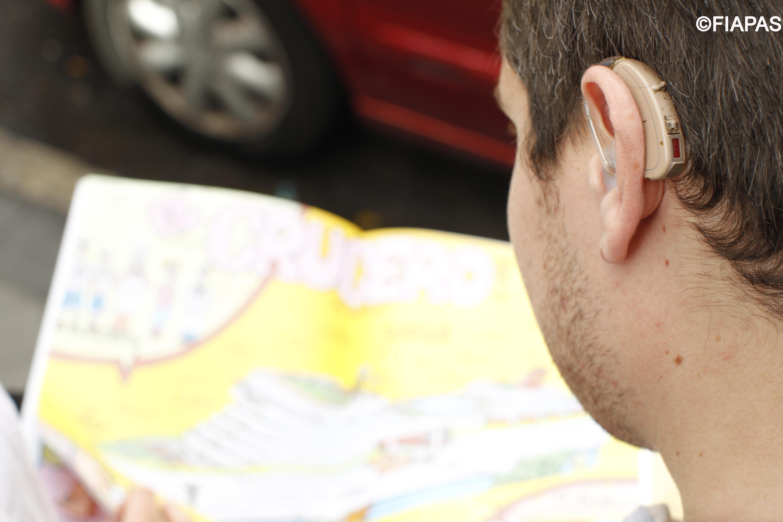 Imagen de un joven portando un audífono en su oreja izquierda