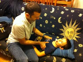 El fisioterapeuta Antonio Ríos con Ángel, un niño de 8 años con fibrosis quística.