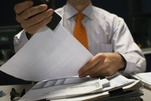 Businessman Stapling Documents --- Image by © Todd Warnock/Corbis